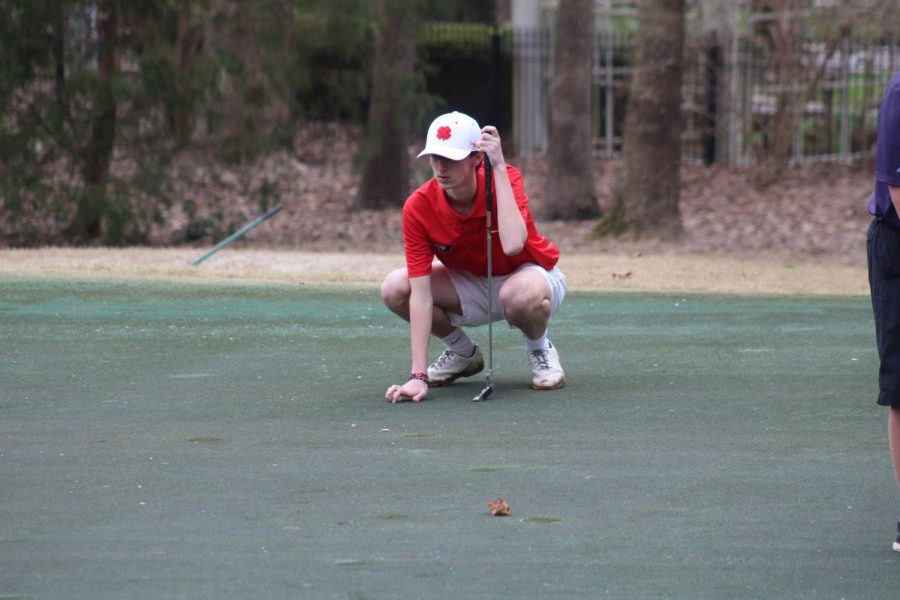 Senior Jack Butler attempts to read the green before a crucial par putt
